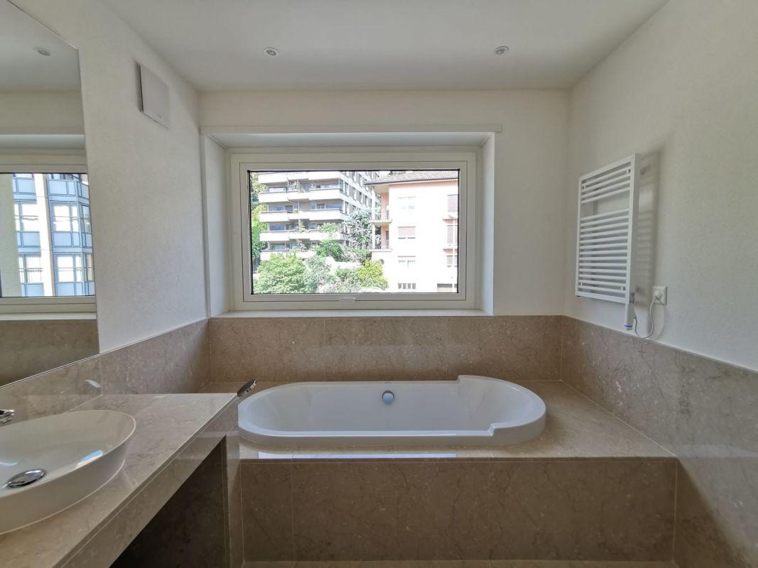Bagno con vasca, finestra e rivestimento e pavimento in marmo botticino
