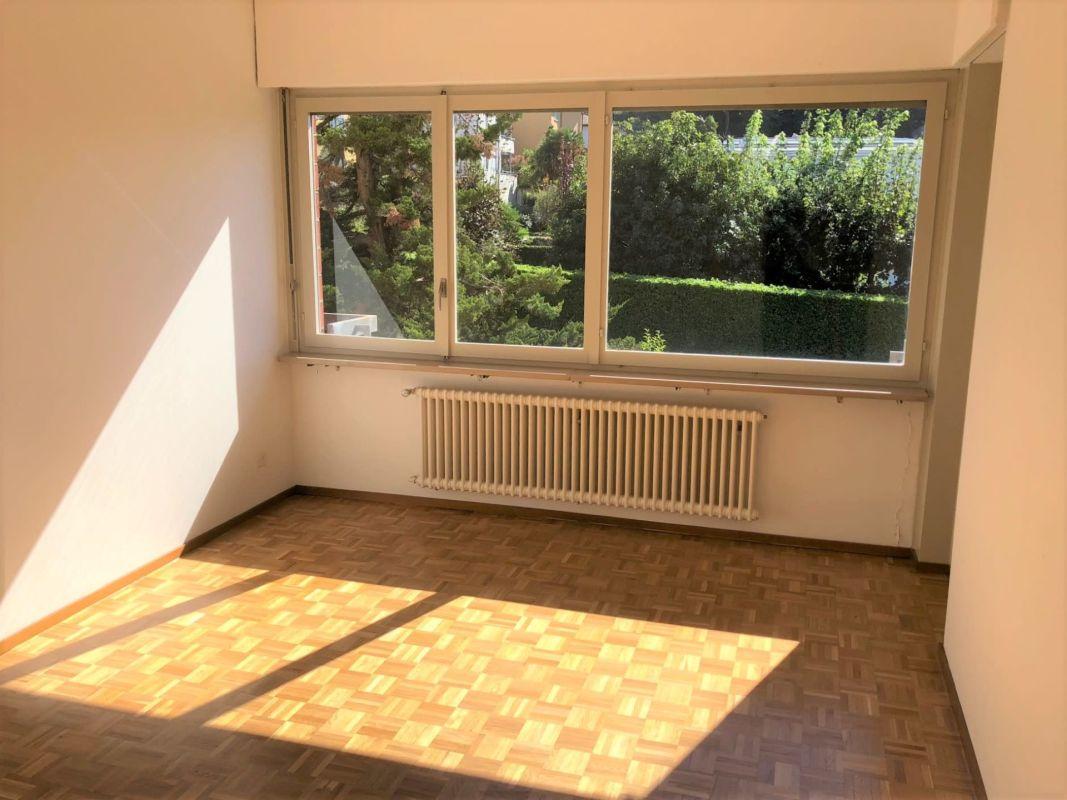 Camera con pavimento in parquet e finestra