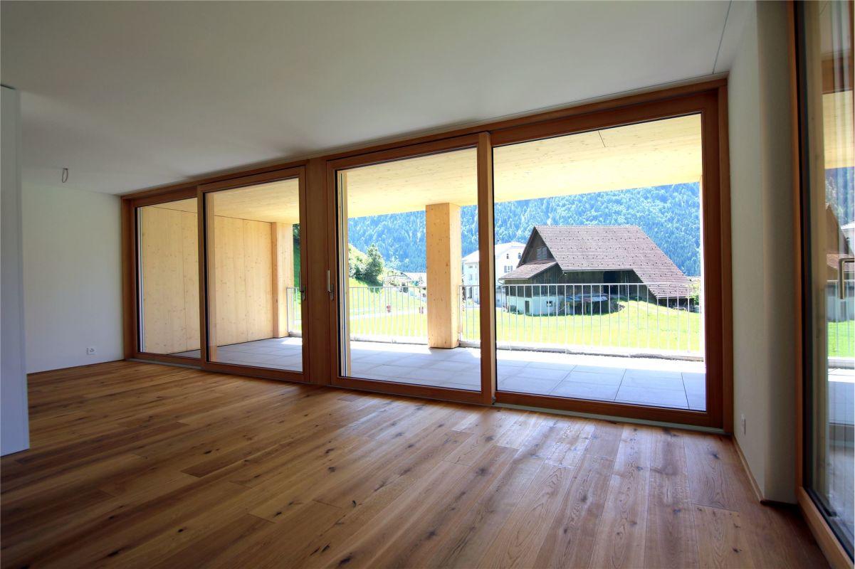Wohnzimmer mit Zugang zu gedecktem Balkon
