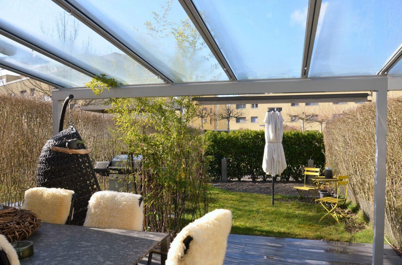 überdachter Gartensitzplatz mit Rasenfläche